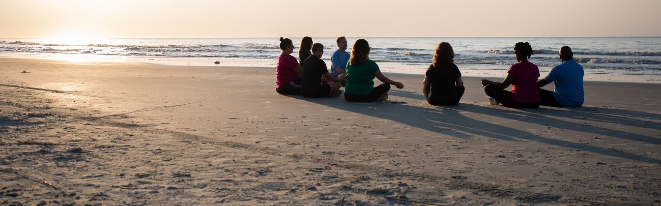People Meditating on the Beach